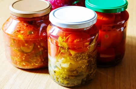 tinned: several jars of tinned vegetables on a wooden domestic table