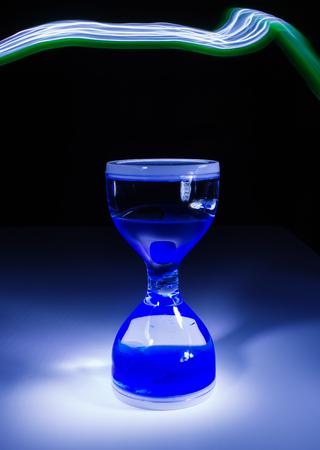 down beat: sand glass clock on black background low key