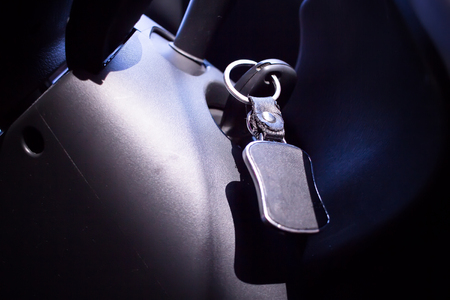 keyless: key in ignition cars with leather keychain blur close-up