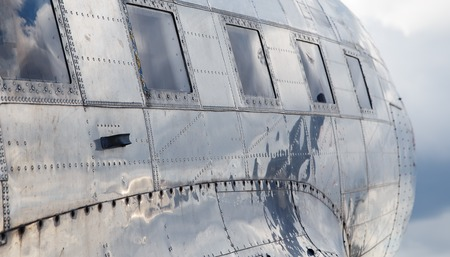 aluminum airplane: square windows of the old airplane sunny day reflection of the sky in aluminum casing Stock Photo