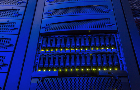 diskdrive: rack with blade behind bars mainframe in data center