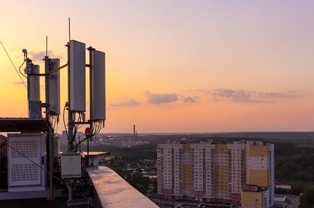 市と夏の夕日を背景に携帯電話通信タワー