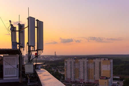 cellular communications tower on a background of the city and beautiful sunset in summer