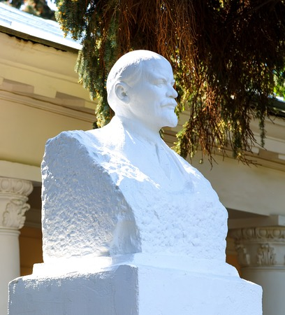 plaster bust of Lenin on background of green summer sunny weather Stock Photo