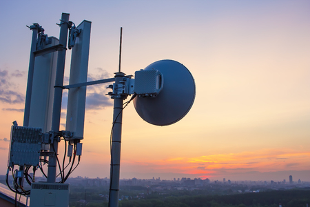 base station with a radio relay antenna on the background of a sunset over the city Foto de archivo