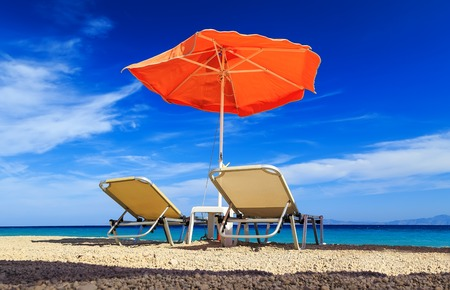 deck chairs: deck chairs and umbrella on background of sea and pebbles