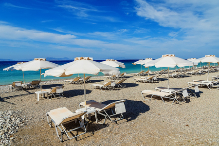 idling: colorful beach umbrellas with deck chairs pebble beach and island in distance