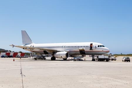 Airplane in airport serviced by ground crew Standard-Bild