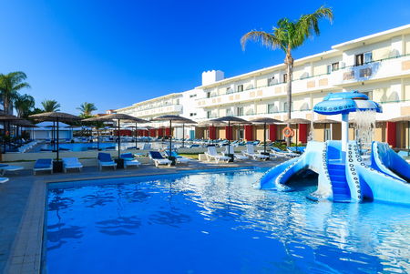 Space by pool with sun loungers and childrens playground with slides