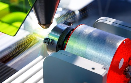 ablaze: Laser cutting of metal on a lathe with program. Stock Photo