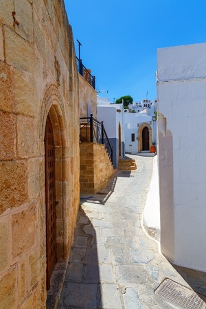 Traditional street with white houses in Lindos village, Rhodes island, Dodecanese