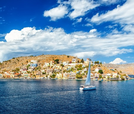 sailing yacht in the beautiful buildings of Symi , clouds, sky, bright Sunny day