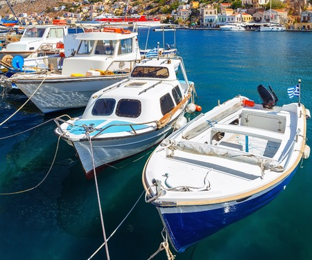 dodecanese: Traditional Greek fishing boats in harbour at Symi Town in the Dodecanese Greece Europe Stock Photo