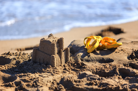 water s edge: sand castle and childrens flip-flops for the beach