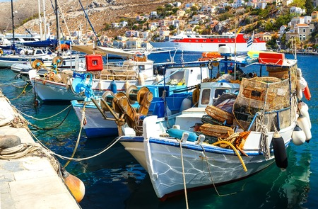 docked: traditional small fishing boats docked in the main port of Symi island in Greece