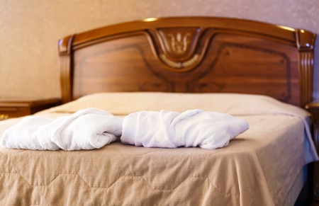 housecoat: two white Terry robe on edge of a vintage bed of brown wood in a modern hotel
