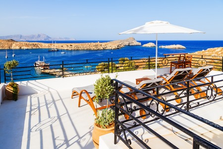 Breathtaking view on bay with beach and ships from a balcony in Lindos, Rhodes, Greece. Stock Photo
