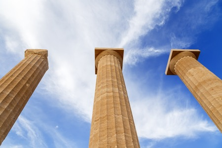 Three ancient greek pillars against a blue sky