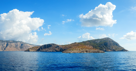 ancient atlantis: Blue sky and sea landscape with mountains and white clouds