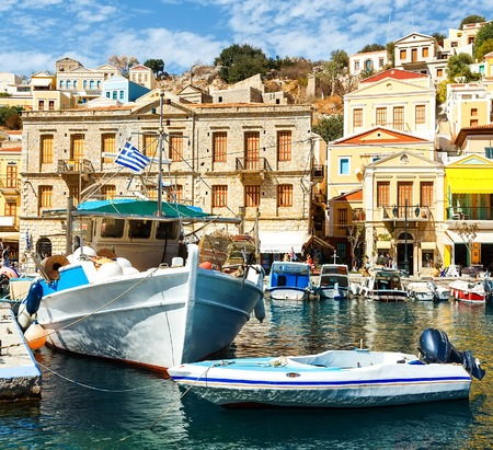 Symi island - Colorful houses and small boats at heart of the village Stock Photo