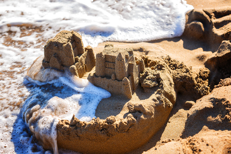 waves wash away sand castles on the beach the sea