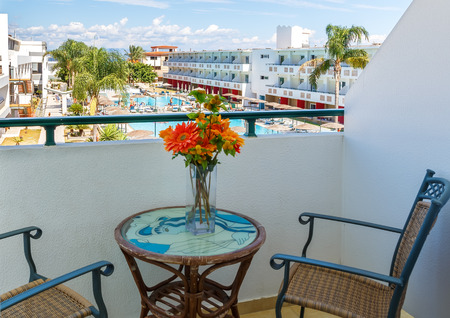 baranda para balcon: Balcony with chairs and table overlooking swimming pool at luxury tropical hotel Foto de archivo