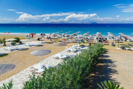 White wooden walkway on beach including umbrellas with deck chairs. Aegean Sea. Greece Rhodes.
