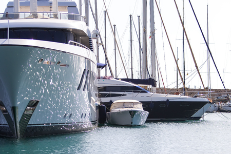 huge sailboat and small motor boat at pier of the port of Rhodes