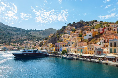 Bay of Symi, with ships and rich blue sky with clouds Stock Photo