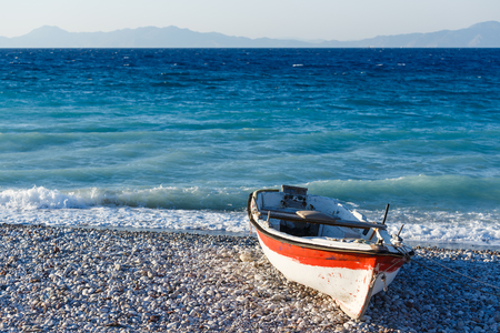 white wooden fishing boat on the shore of a pebbly beach Greece Rhodes Stock Photo
