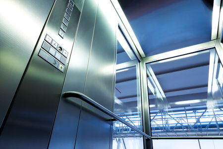 metallic stairs: Inside metal and glass Elevator in modern building , the shiny buttons and railings Stock Photo