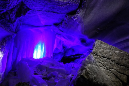 ice stalactites blue color in cave in stunning texture of rock, covered with frost