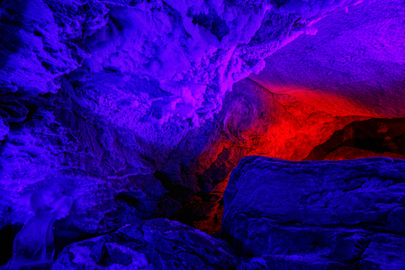 beautiful illuminated blue and red stalactites from karst cave.