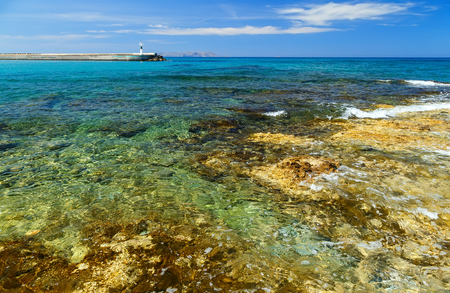 Waves break on rocky shore. Coast and beach resort village. Clear day at sea. Stock Photo