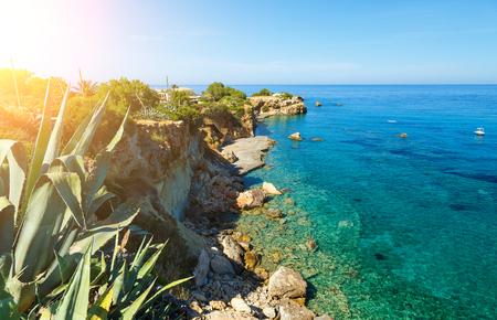 Waves break on rocky shore. Coast and beach resort village. Road along a rocky cliff. Tourist beach resort in village Crete island, Greece.