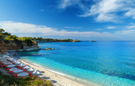 beach with white sand and clear blue water in beautiful Bay with sun beds and umbrellas, Crete, Greece Stockfoto