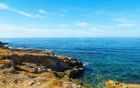 Volcanic rock on shore of the island of Crete Greece, cloud sun weather
