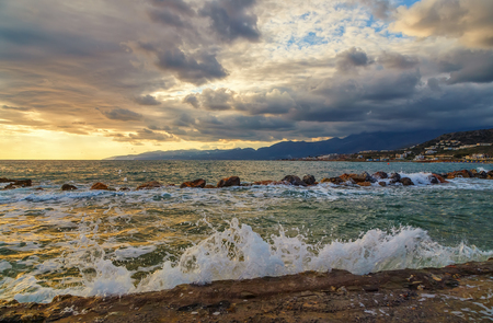 sunrise with a beautiful multi-colored clouds and waves lapping on the shore in the foreground, Crete Greece