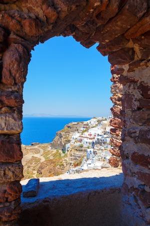 Windmill through an old window in Santorini island, Greece Imagens