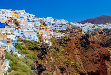 Image of white city on a slope of a hill at sunset, Oia, Santorini, Greece