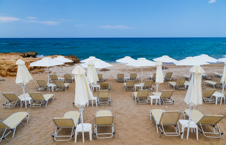 Sandy beach with parasols and beach loungers Crete Stock Photo