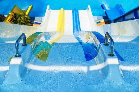 View from top on colorful plastic water-slide in swimming pool. Blur aperture Stock Photo