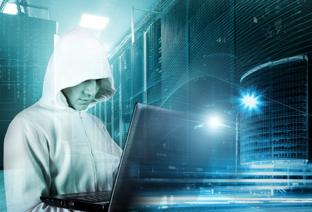 hacker in hood with a laptop in hand on background of rows of servers, data center and skyscrapers of the city at night Banco de Imagens - 85106379