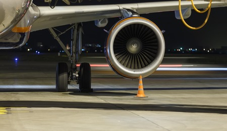Engine and chassis of passenger jet plane in the night. Front view. Aircraft air intake and fan blades close up. Stock Photo