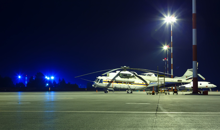 large cargo helicopter in the Parking lot at the airport the night among the lights