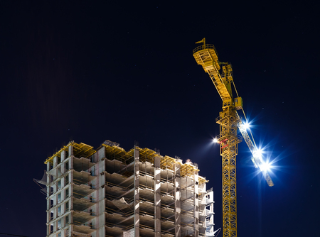 unfinished building: Building under construction illuminated at night