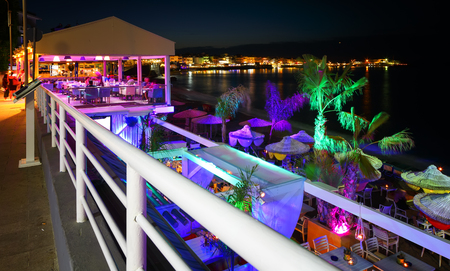 Beautiful evening with night shore with a beach and umbrellas and highlighted with bright colorsin Hersonissos bay Crete, Greece Banco de Imagens - 90332093