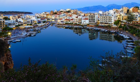 Beautiful southern town of Agios Nikolaos at summer evening. Boats swing on the water of the lake Voulismeni at the pier with evening lights. Crete Island. Greece Banco de Imagens