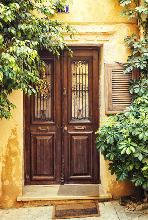 old wood brown pictorial greek doors with flowers and trees on the sides, Chania, Crete, Greece Stock Photo