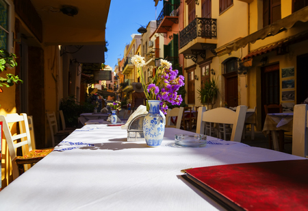traditional Greece series - street tavernas white tablecloth on the table on the background of old streets, depth of field, blur
